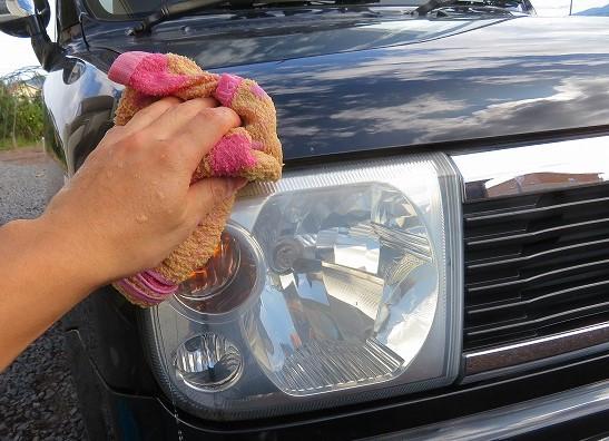 車のヘッドライトをタオルで拭く